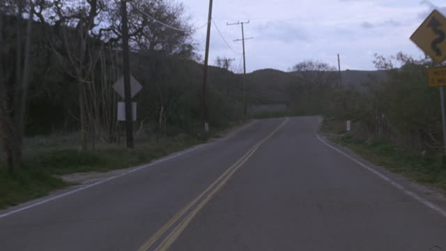 POV Driving on a winding, hilly road in early morning, and two dark sedans swinging across the road to block it / Santa Monica, California, United States