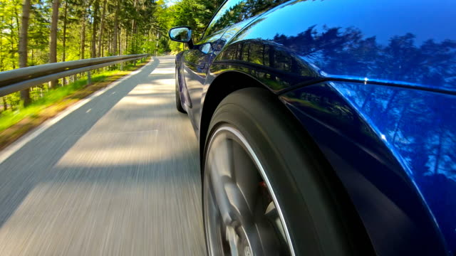 driving on a winding mountain road surrounded by green scenery - sports car stock videos & royalty-free footage