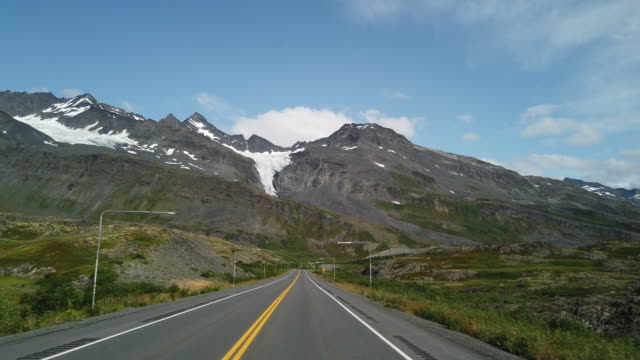 driving on alaska mountain road with glacier mountain ahead - mountain road stock videos & royalty-free footage