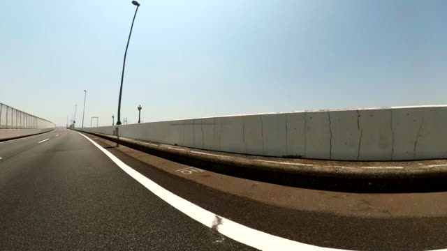 driving on an empty highway at sunny day / rear view shot from car. - fence stock videos & royalty-free footage