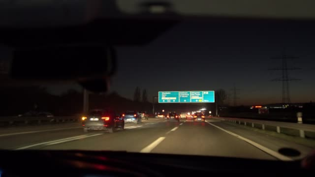 driving on autobahn a66 at dusk - road sign stock videos & royalty-free footage