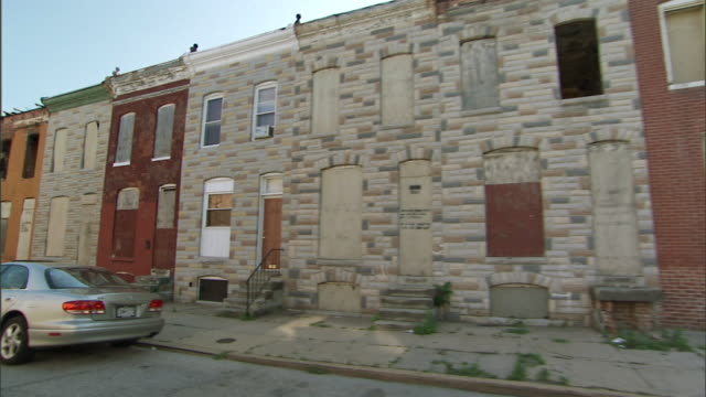 hd driving on blighted neighborhood street empty row houses all but one w/ windows doors boarded africanamerican male w/ head in hand sitting on... - baltimore maryland bildbanksvideor och videomaterial från bakom kulisserna