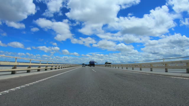 Driving on bridge with clouds