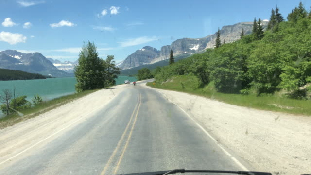 driving on bumpy road in us glacier national park - glacier national park us stock videos and b-roll footage