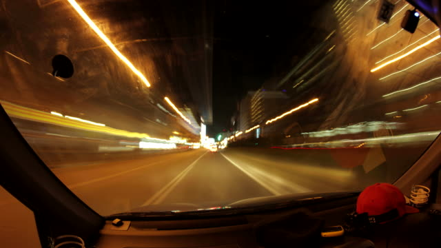 POV T/L driving on busy city streets at night.