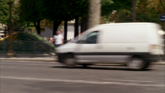 vidéos et rushes de ds driving on city road passing vehicles and pedestrians / paris, france - dolly shot