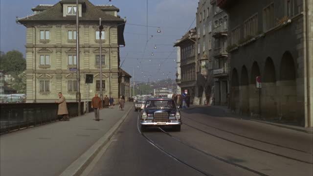 1966 REAR POV Driving on city street / Zurich, Switzerland