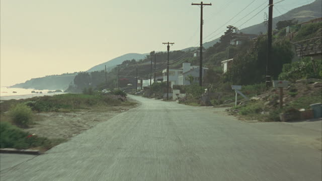 1965 rear pov driving on coastal road, passing by beach cottages / california, usa - telegraph pole stock videos and b-roll footage