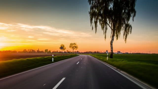 pov driving on country road in germany at sunset - tarmac stock videos & royalty-free footage