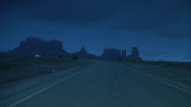 rear pov, driving on desert road at dusk  - butte rocky outcrop stock videos and b-roll footage