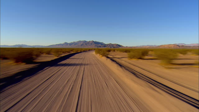 pov, driving on desert road, jackass, nevada, usa - schotterstrecke stock-videos und b-roll-filmmaterial
