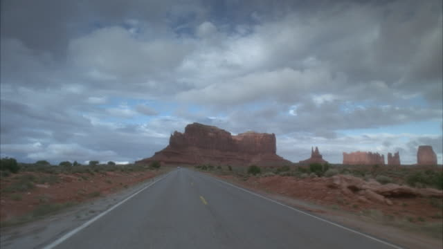 rear pov, driving on desert road  - butte rocky outcrop stock videos and b-roll footage