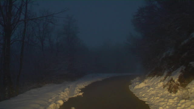 POV Driving on foggy snow covered mountain road at dusk, Pyrenees, Spain