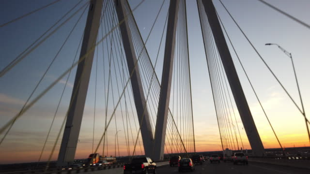 driving on fred hartman bridge at sunset - suspension bridge stock videos & royalty-free footage