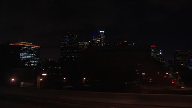 driving on freeway past los angeles high-rises at night, passenger pov - 車の視点点の映像素材/bロール