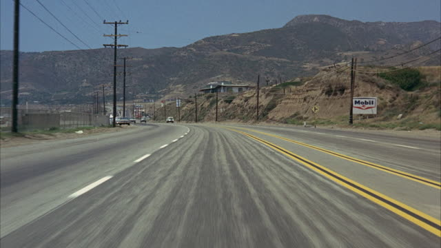 1965 rear pov driving on highway 101 in mountain landscape in the vicinity of zuma beach, malibu / california, usa - small town stock videos & royalty-free footage
