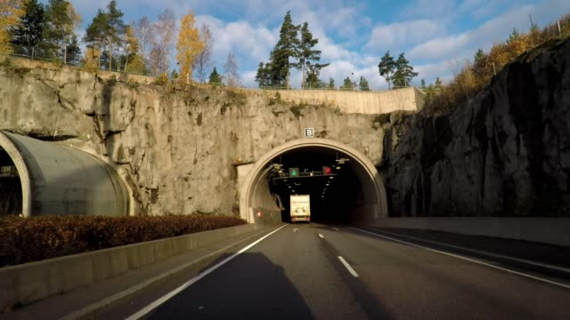 vidéos et rushes de driving on highway going under a bridge and into tunnel helsinki, finland - car point of view