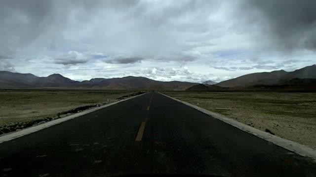 driving on highway through tibetan plateau - tibetan plateau stock videos & royalty-free footage