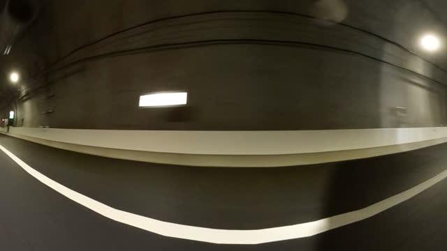 vidéos et rushes de conduite sur le tunnel d'autoroute / vue arrière et latérale tiré de la voiture. - vue latérale