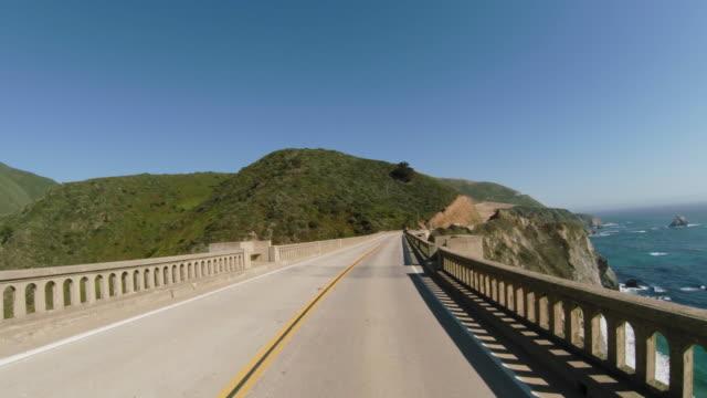 driving on historical bixby bridge along the legendary pacific coast highway in california. - bixby creek bridge stock videos & royalty-free footage