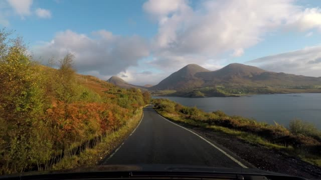 vídeos de stock, filmes e b-roll de driving on idyllic country road beside coastline loch with blue sky and clouds, isle of skye, scotland - loch