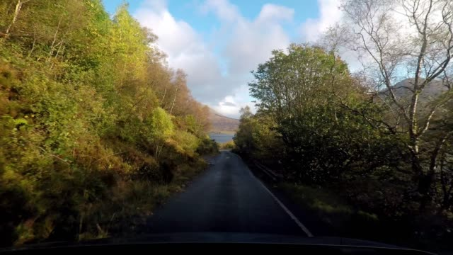 Driving on idyllic country road beside coastline loch with blue sky and clouds, Isle of Skye, Scotland