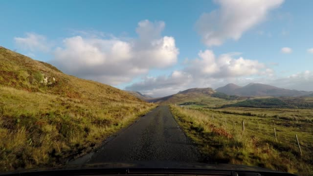 Driving on idyllic country road with blue sky and clouds, Isle of Skye, Scotland