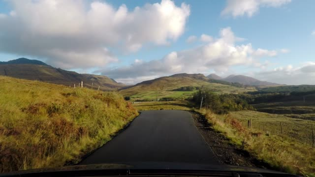 vídeos de stock, filmes e b-roll de driving on idyllic country road with blue sky and clouds, isle of skye, scotland - ponto de vista de carro
