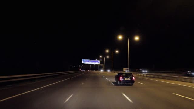 pov driving on m25 motorway with airport directional signs at night / london, united kingdom - m25 video stock e b–roll
