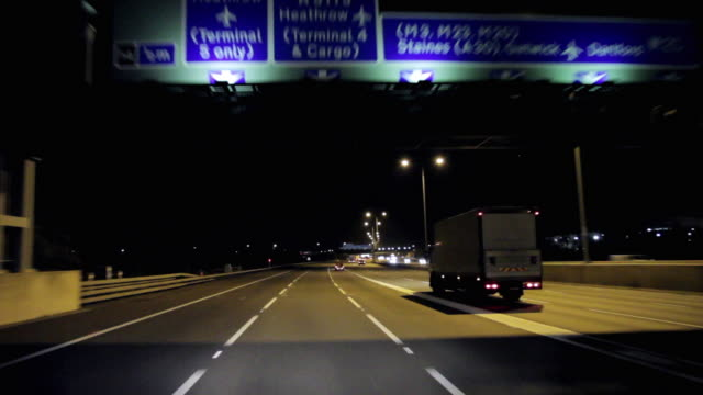 pov driving on m25 motorway with airport directional signs at night / london, united kingdom - sign stock videos & royalty-free footage