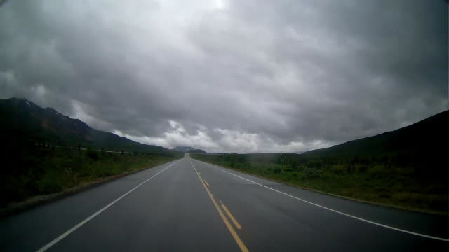 driving on mountain road with snowcapped mountain in the background in a rainy day - 乗物後部から見た視点点の映像素材/bロール