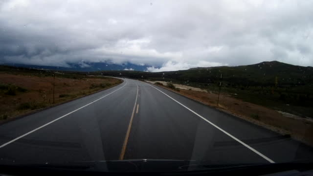driving on mountain road with snowcapped mountain in the background in a rainy day - eternity stock videos & royalty-free footage