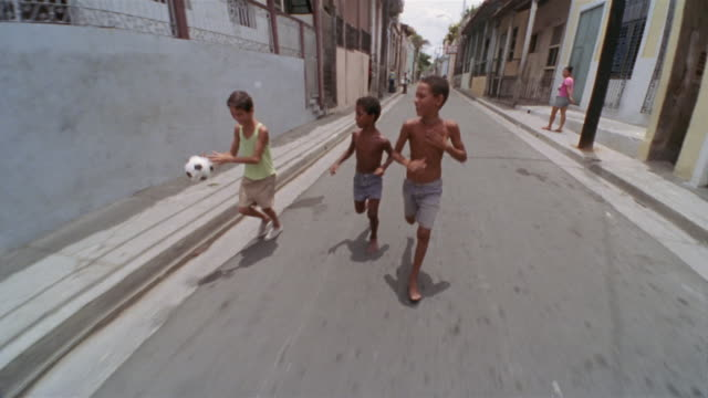 REAR POV, Driving on narrow street, three boys (6-7, 8-9) following car, bouncing football, Santiago de Cuba, Cuba