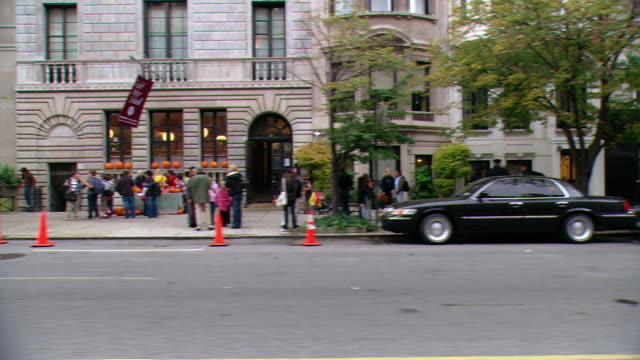 DS Driving on Park Avenue, with traffic, pedestrians, a bus going the opposite direction, a hotel, parked cars, an intersection, and building facades / New York City, New York, United States