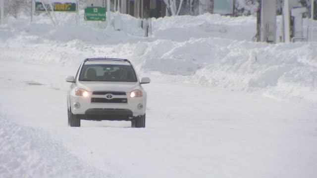 vídeos de stock, filmes e b-roll de suv driving on plowed city street after snowstorm - desaparecer gradualmente