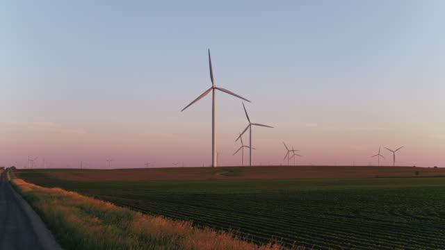 Driving on road near wind farm at sunset