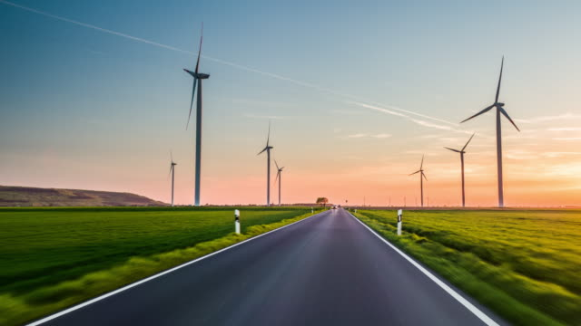driving on road surrounded by wind turbines - diminishing perspective stock videos & royalty-free footage