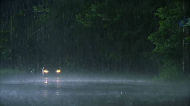 ws pan suv driving on rural road in heavy rain at night - sports utility vehicle stock-videos und b-roll-filmmaterial