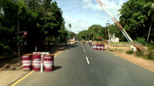 ms pov driving on rural road past walking cattle and roadblocks, pondicherry, india - 通行止め点の映像素材/bロール