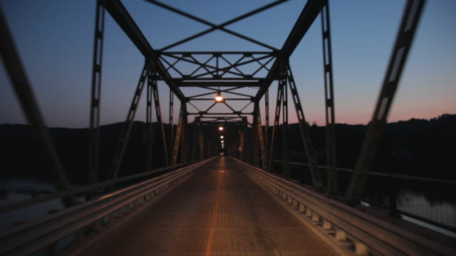 pov driving on steel bridge over delaware river at dusk / frenchtown, new jersey, usa - vanishing point stock videos & royalty-free footage
