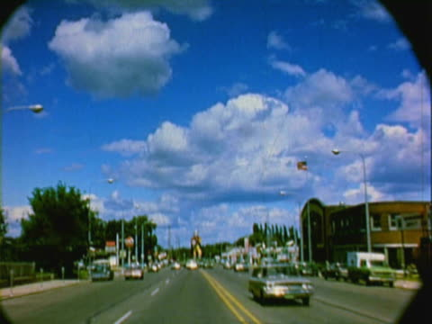 montage pov driving on street in traffic, approaching a towering statue of a giant viking / alexandria, minnesota, united states - 1971年点の映像素材/bロール