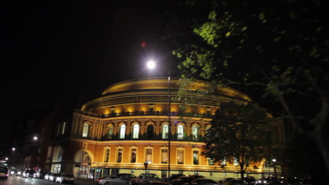 POV Driving on street, passing Royal Albert Hall at night / London, United Kingdom