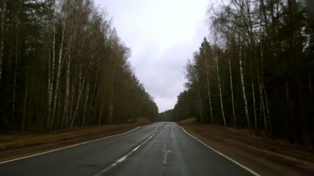 雨の下で高速道路を走行。雨滴によって覆われたフロント ガラスを介してビュー - 散歩道点の映像素材/bロール
