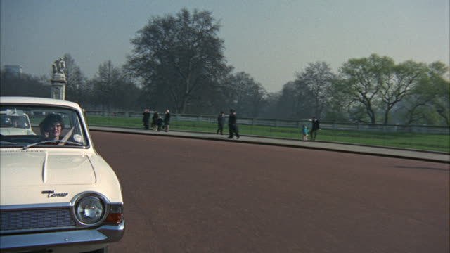 1966 rear pov driving on traffic circle in front of buckingham palace / london, united kingdom - royalty stock videos & royalty-free footage