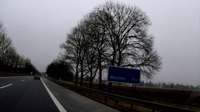 driving on tree lined highway toward munich, germany, europe - verkehrsschild stock-videos und b-roll-filmmaterial
