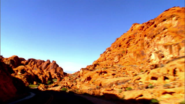 pov driving on two lane desert road through red rocks of aztec sandstone in valley of fire / overton, nevada, usa - sandstone stock videos & royalty-free footage