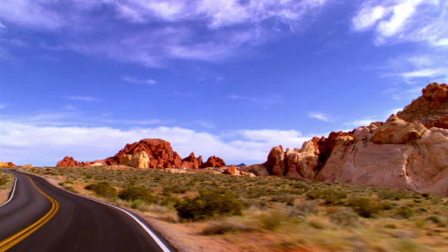 POV driving on two lane desert road through red rocks of Aztec sandstone in Valley of Fire / Overton, Nevada, USA