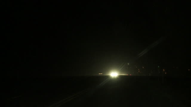 pov of driving on wintery road at night with oncoming traffic. - headlight stock videos & royalty-free footage