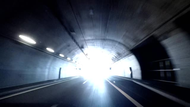 driving out of a modern road tunnel into sunlight, car travel in switzerland - light at the end of the tunnel stock videos & royalty-free footage