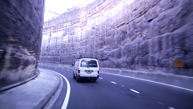 pov driving out of tunnel and between steep cliff walls in city - curve stock videos & royalty-free footage